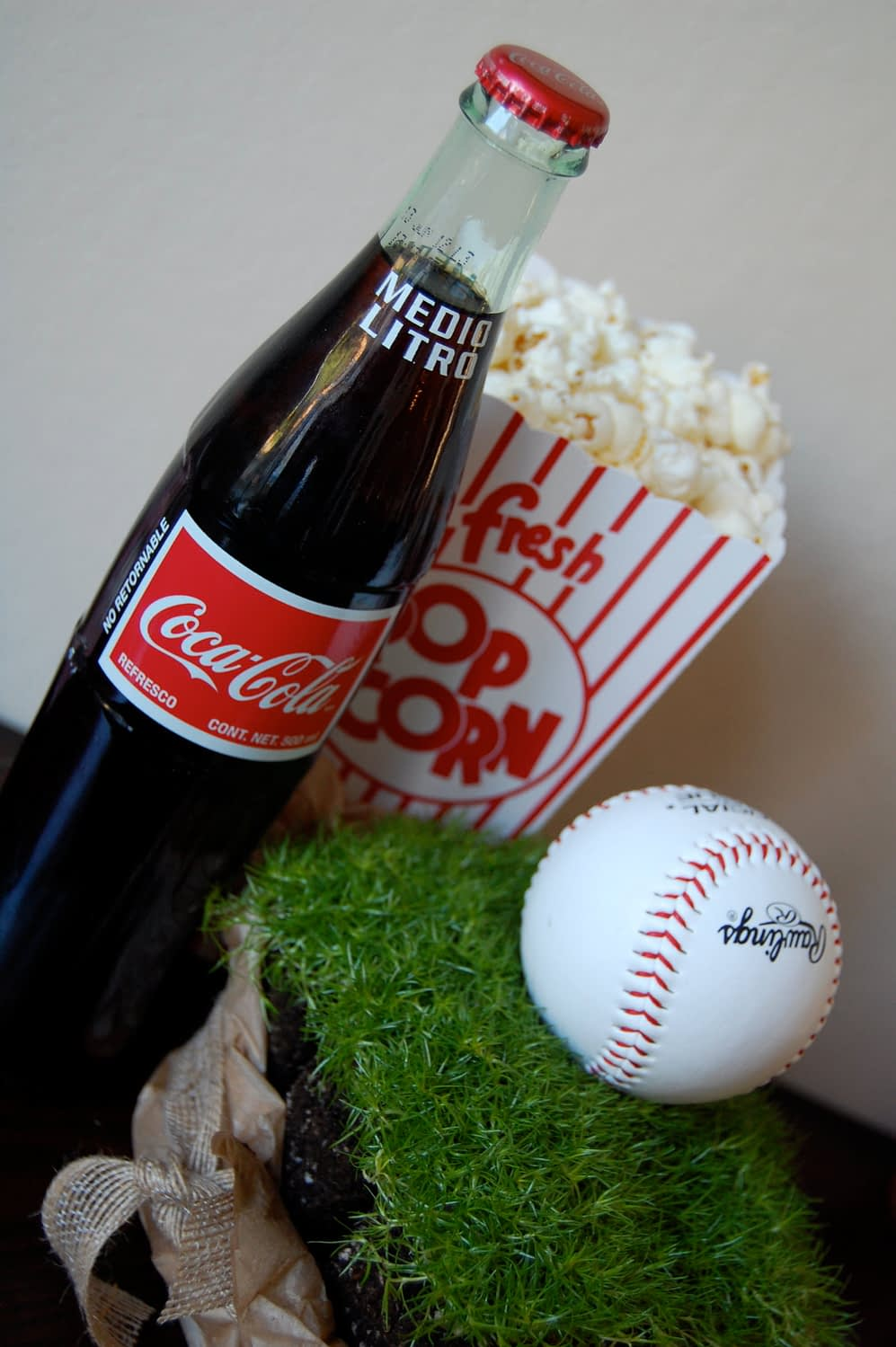 """Retro Coke bottles I found in small markets and simply used cardboard popcorn boxes, stuffed halfway with tissue paper and then topped with popcorn! The """"real baseball turf"""" was bought from Home Depot. It was actually a tray of square ground cover and I wrapped each one in brown tissue, tied with a ribbon. So easy and oh Sooooo cute! People went crazy over it!"""