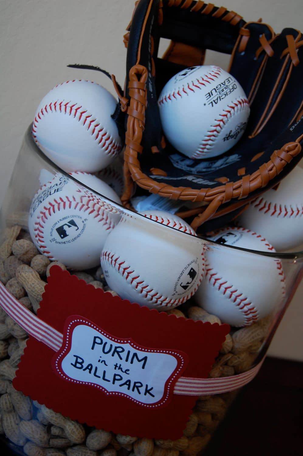 An easy Buffet Table center piece...A large glass cylinder vase, punch bowl, filled with peanuts. Then add baseballs, a baseball glove and another ball! You can either purchase baseballs from sports stores (if you know your boys will enjoy future use out of them!) or you can order fake cheaper ones from bulk stores like oriental trading. Even the squishy stress ball ones would work! I Wrapped a ribbon around it with a paper card in red and a label...keeping with my color scheme. You can add a box under the table linen to give it even more height if you wish. (If you are worried about Peanut allergy, try using popcorn or only baseballs).
