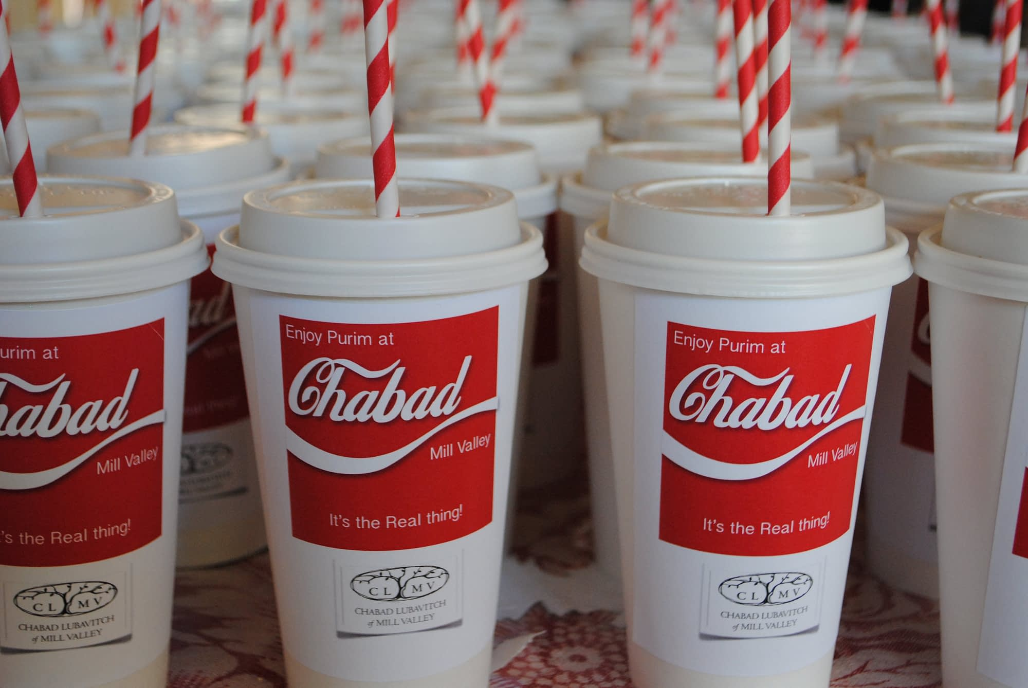 Ok, I had the most fun with these!! I bought plain paper white soda cups with lids and red and white striped straws.  I filled the cups with nosh, hamantashen etc. and stuck a mailing address on top which I designed and printed in color. These were so easy and just so fun!!