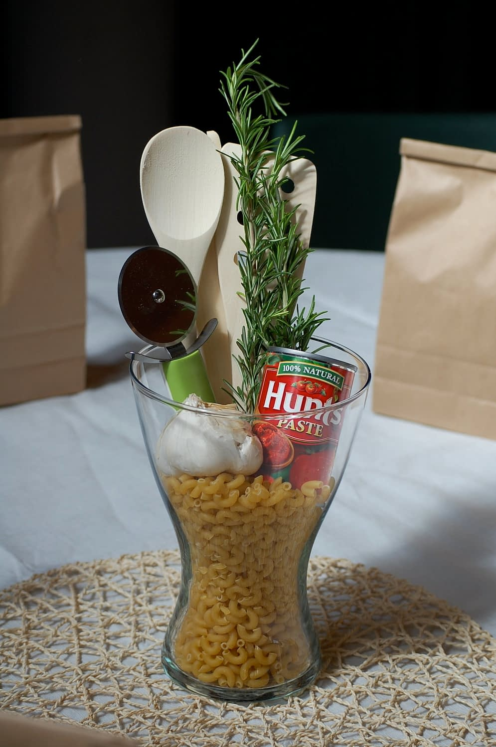 A simple glass vase from Ikea, filled with macaroni elbows (large bag from Smart & Final), a pizza cutter and wooden spoons from Ikea, a bundle of Rosemarry, a can of Hunts Tomatoe Paste and a fresh bulb of garlic! The base of the center piece was a placemat that I found at Ikea that looked like spgahetti to me:)